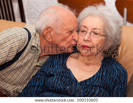 Elderly 80 plus year old couple in an affectionate pose in a home setting. - stock photo