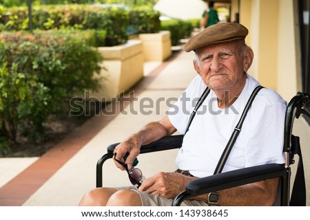 Elderly 80 plus year old man in a wheel chair outdoors.