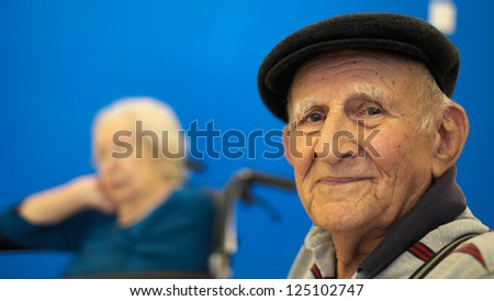 Elderly 80 plus year old man portrait with a blue background.