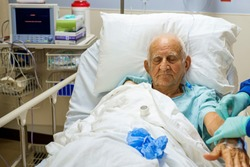 Elderly 80 plus year old man recovering from surgery in a hospital bed.