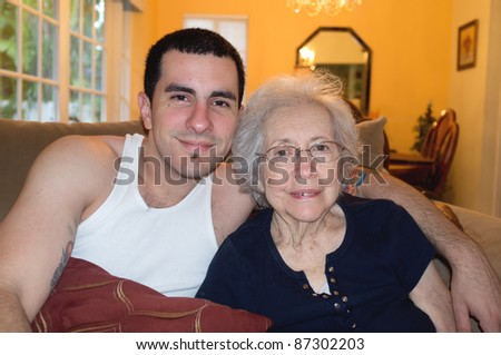 Elderly 80 plus year old woman with Alzheimer and her grandson in a home setting.