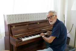 Elderly practice to play piano in house alone