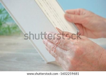 Elderly reading.  Elderly hands and book