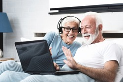 Elderly retired couple talking over skype with their son who living far away over the ocean. Senior woman has in-ear headphones with a microphone. Concept maintaining distance contact.