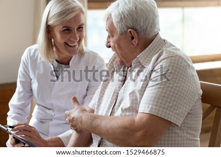 Elderly 80s man patient and middle-aged nurse medical worker holding clipboard writing personal information having pleasant warm conversation talk with clinic client nursing caregiving service concept