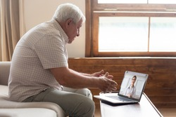 Elderly 70s man seated on sofa make distant video call, senior patient look at laptop screen communicating with doctor therapist online, older generation and modern tech application easy usage concept