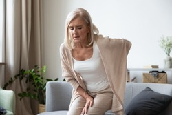 Elderly 60s woman got up from couch felt severe painful feelings in lumbar, massaging low back to reduce ache, suffer from backache discomfort, diseases of older people, sciatic nerve injury concept