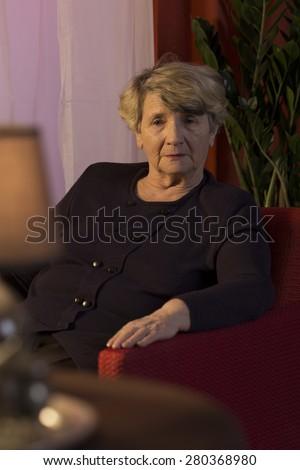 Elderly sad lady sitting in solitude in dark room