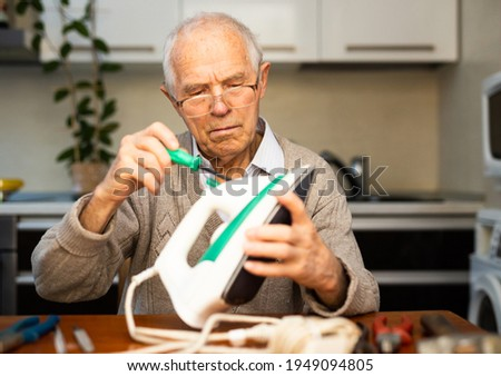 elderly señor fix the iron at table Foto stock ©