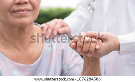 Elderly senior dementia patient (aging old adult person) in nursing hospice home holding geriatrician doctor's hand having happy medical health care from hospital carer or caregiver healthcare service #1076284586