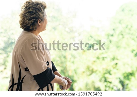 Elderly senior female using walking stick or walking cane staff standing beside window in domestic living room - recovery and rehabilitation concept