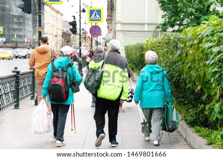 Elderly senior women practicing nordic walking in the city, healthy lifestyles in old age. Old pensioners walk with sticks along the street. Sports walks on a summer sunny day.