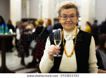Elderly Senor drinking champagne and relaxing at lobby of theater at intermission Stock photo ©