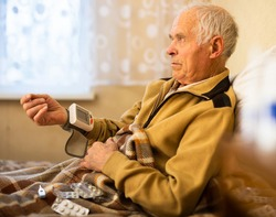 Elderly Senor measuring pressure with tonometer at Home
