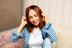 Elderly smiling female in headphones listening to music. She is buying it in appstore on cyber monday. Woman closes her eyes cause she like this music and lifestyle
