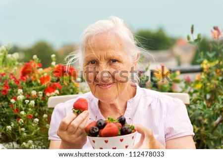 Elderly smiling woman sitting on a terrace, holding a bowl with strawberry and cherries