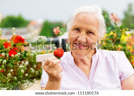 Elderly smiling woman sitting on the terrace, holding a strawberry