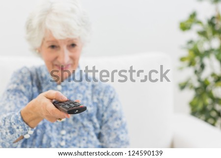 Elderly smiling woman using the remote on a sofa