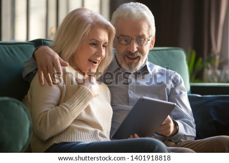 Elderly spouses sitting on sofa look at digital tablet screen feels stunned, happy aged couple open mouth amazed by promotional e-mail medicine clinic services better offer, online lottery win concept