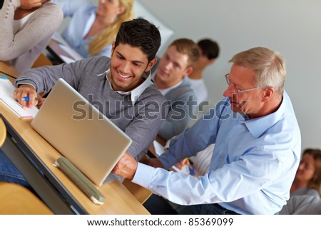 Elderly teacher giving assistance in university class
