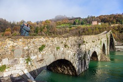 Elderly tourist photographs a magnificent landscape. Ponte della Maddalena Bridge. Cold green waters of the Sercchio River. Italy. Province of Tuscany. Cold windy winter day