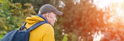 elderly traveler wearing green cap and yellow hoodie with black rucksack walking in mountains and forest at sunset side view
