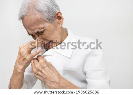 Elderly was sniffing her clothes smell musty or shirt smell moldy,bad smell,foul odor from washing,unclean laundry,senior woman is smelling stinky,scent detergent,pungent fragrance of fabric softener Stockfoto ©