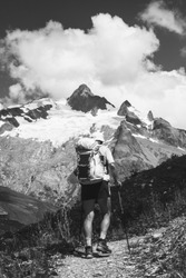 Elderly wellness concept. Senior man hiking French Alps in summer with solar backpack.  Aiguille des Glaciers, Mont Blanc mountains. View from Chapieux valley, Savoie, France. Black white photo
