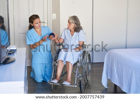 Elderly woman after a stroke in a wheelchair during physiotherapy with the hedgehog ball in the rehab clinic Foto stock ©