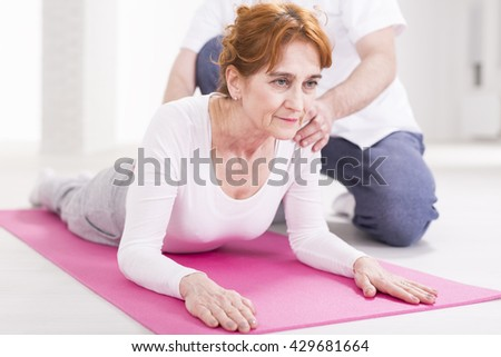 Elderly woman after injury stretching her spinal during rehabilitation. Next to her physical therapist helping with exercise