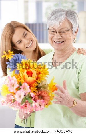 Elderly woman and daughter smiling happily at mother's day, having flowers.?