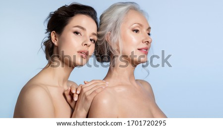 Elderly woman and young woman with perfect skin portrait. Young daughter standing behind older mother putting hand on arm looking at camera. Different age generation family bonding. Beautiful people
