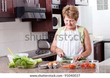 elderly woman cooking food in home kitchen