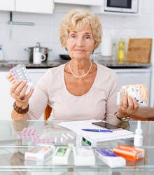Elderly woman counting her expenditure on medicines sitting in kitchen
