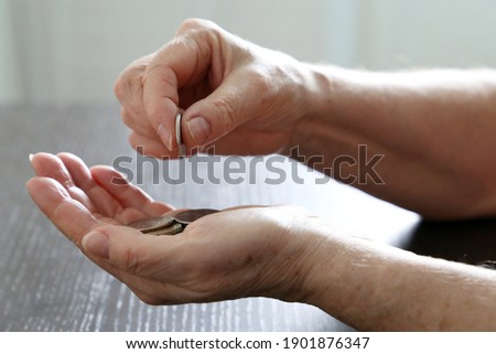 Elderly woman counts coins, wrinkled female hands with metal money closeup. Concept of poverty, pension payments, pensioner