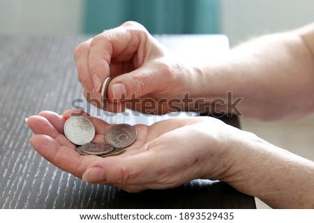 Elderly woman counts russian rubles in coins, female hands close up. Concept of poverty in Russia, pension payments, pensioner with metal money