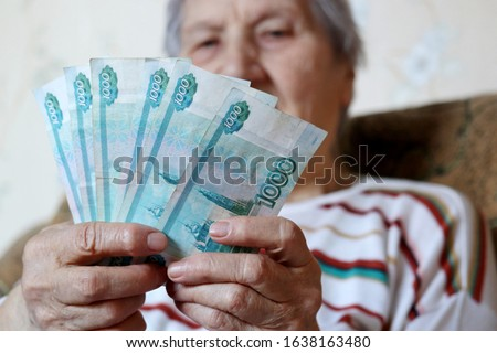 Elderly woman counts russian rubles in hands. Pension payments, retirement savings or benefits concept, female pensioner with paper currency of Russia