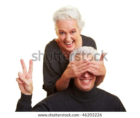 Elderly woman covering the eyes of her husband