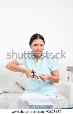 Elderly woman cutting credit card with scissors in living room