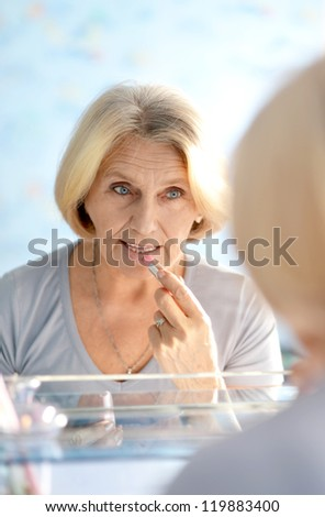 elderly woman doing make-up in the bathroom