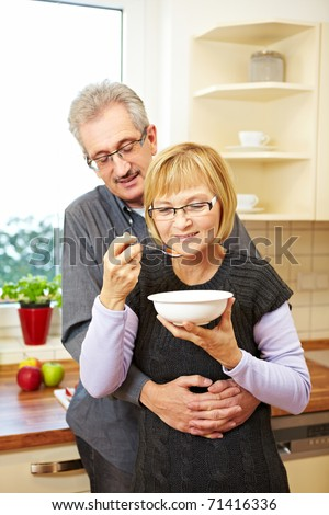Elderly woman eating muesli in the kitchen while husband is embracing her