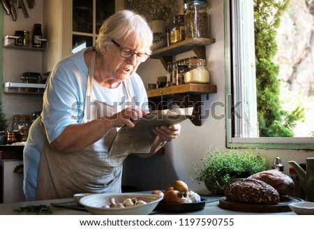 Elderly woman following a cookbook in the kitchen