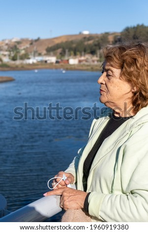 elderly woman, grandmother, walking in a natural place, looking at the horizon relaxed, vertical photo