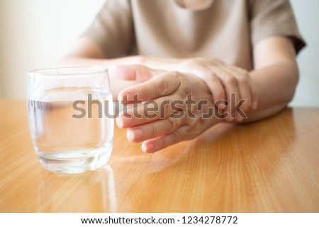 Elderly woman hands w/ tremor symptom reaching out for a glass of water on wood table. Cause of hands shaking include Parkinson's disease, stroke or brain injury. Mental health neurological disorder.