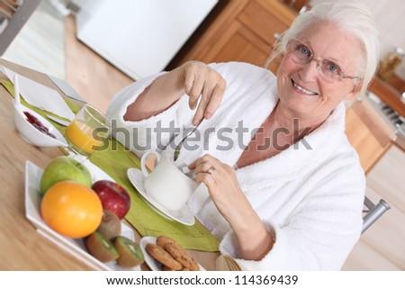 Elderly woman having breakfast - stock photo