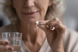Elderly woman hold white round pill and glass of natural water close up image. Senior female taking medication for aging-associated senile diseases prevention, such as dementia atherosclerosis concept