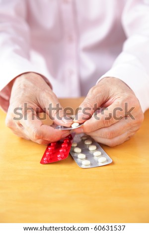 elderly woman holding pills