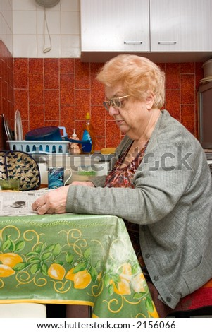 Elderly woman in a small apartment kitchen reading her morning paper while she has her tea.