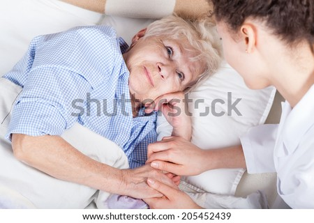 Elderly woman in bed and her nurse