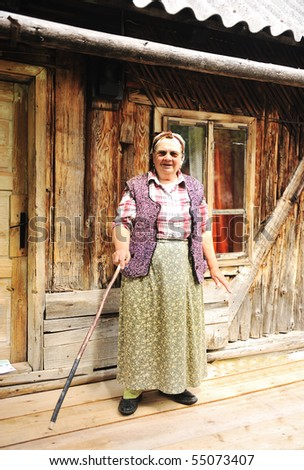 Elderly woman in front of her old house standing with wooden stick in hand